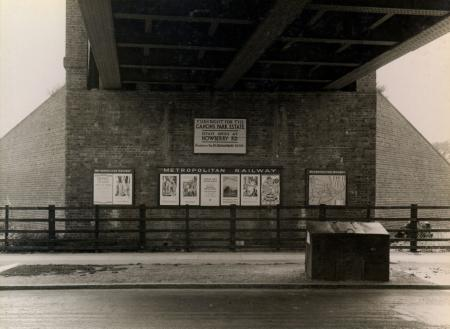 B/w glass neg, metropolitan railway underground poster and underground map panels displayed on the abutment wall of canons park underground station railway bridge by topical press, 25 jul 1933
