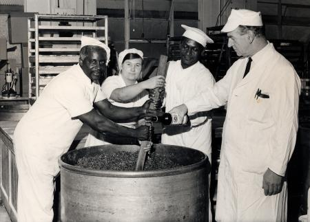 B/w print; edson braithwaite, valerie coppleston, aston benjamin & fred lawrence mixing a pudding at the food production centre in croydon, by london transport, 1971