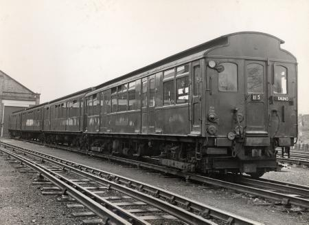 B/w print; three-quarter side view of a four car q23-stock train at an unknown location; the unit nearest the camera is no 4248 by colin tait, 6 dec 1965