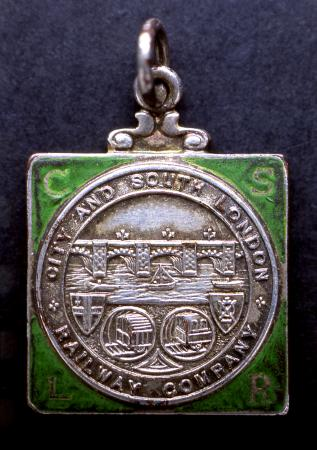 Related object: Pass; silver metal medallion pass with green enamel infill, issued by the City & South London Railway to Rt Hon Lord Aberconway, circa 1911