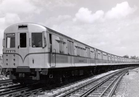 BW print; Three-quarter front view of an eight-car train of unpainted aluminium R49-stock by John Somerset Murray, Jul 1953